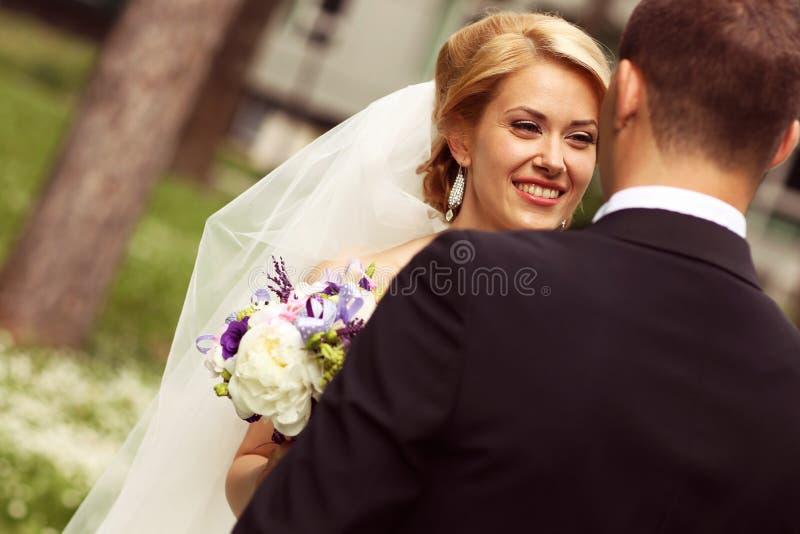 美好的新娘夫妇获得乐趣在他们的婚礼之日花花束的公园 库存照片
