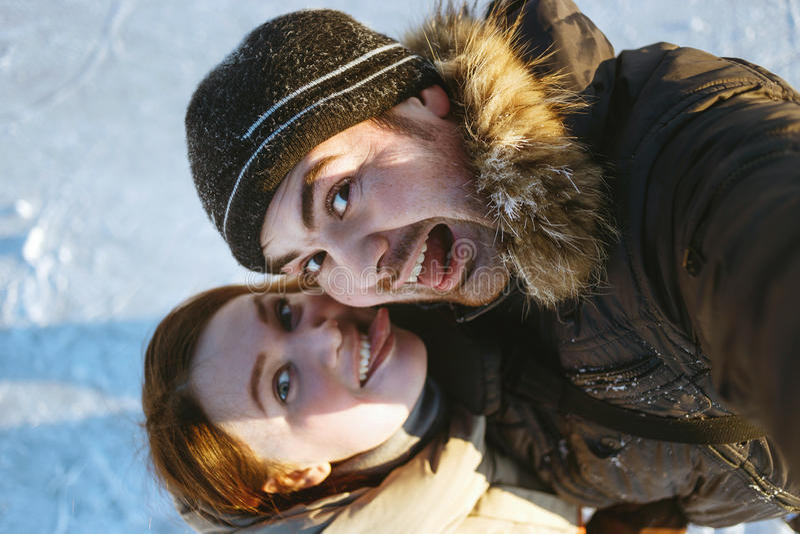 美好的旅行的夫妇、远足者笑的夫妇、情感人和舌头女孩,疯狂的selfie,远足者冬天画象  库存照片