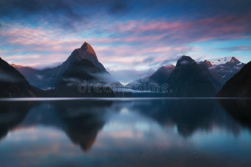 美好的日出在Milford Sound,新西兰 主教峰顶是米尔福德峡湾偶象地标在峡湾国家公园 库存图片