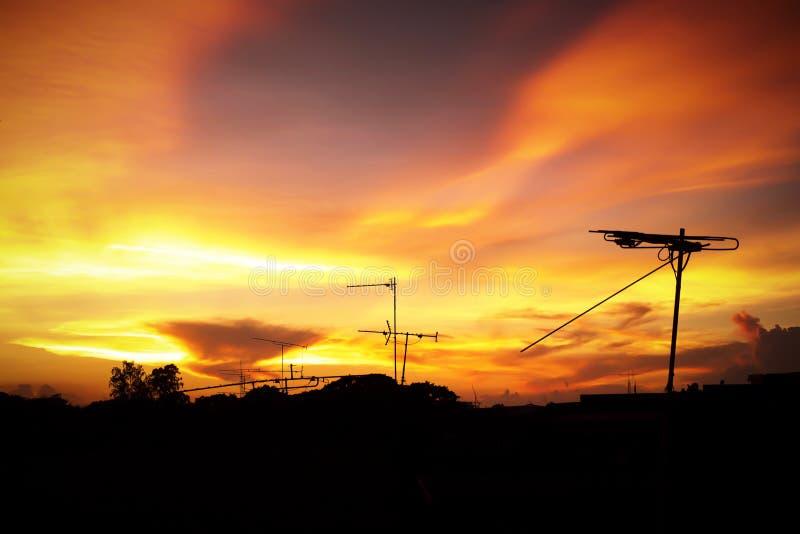 美好的日落剪影与电视天线或电信的耸立,与云彩的橙色天空 库存图片