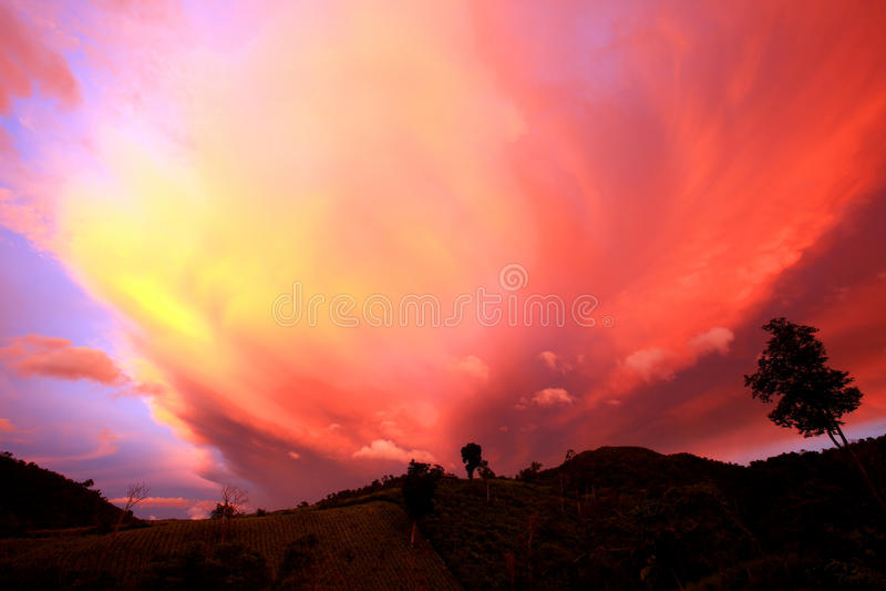 美好的日落和云彩在雨以后与微明和山 免版税库存照片