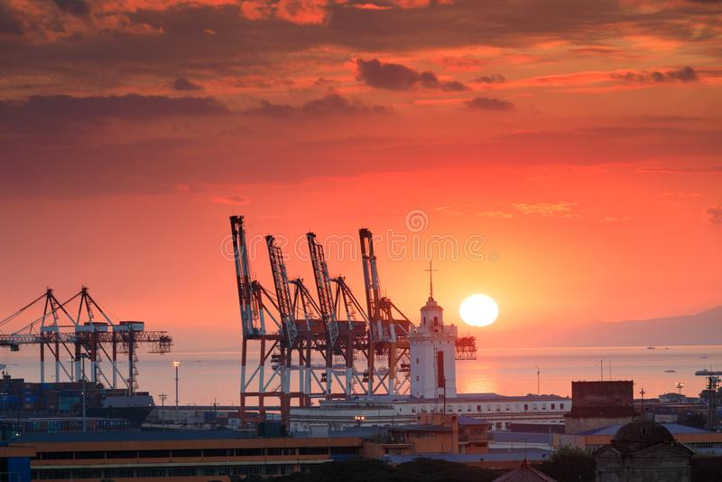 美好的日落和工业货物起重机在马尼拉海湾 库存照片