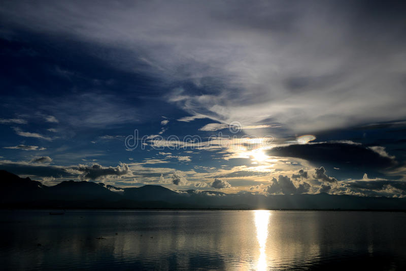 美好的日落和晚上天空与山和云彩和日落在湖反射了背景的 乡下风景U 免版税图库摄影
