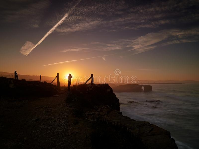 美好的日落和石曲拱在Playa de las Catedrales 库存照片