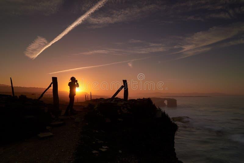 美好的日落和石曲拱在Playa de las Catedrales dur 免版税库存图片
