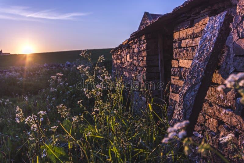 美好的日落在一个老农厂房子的奥克尼 库存图片