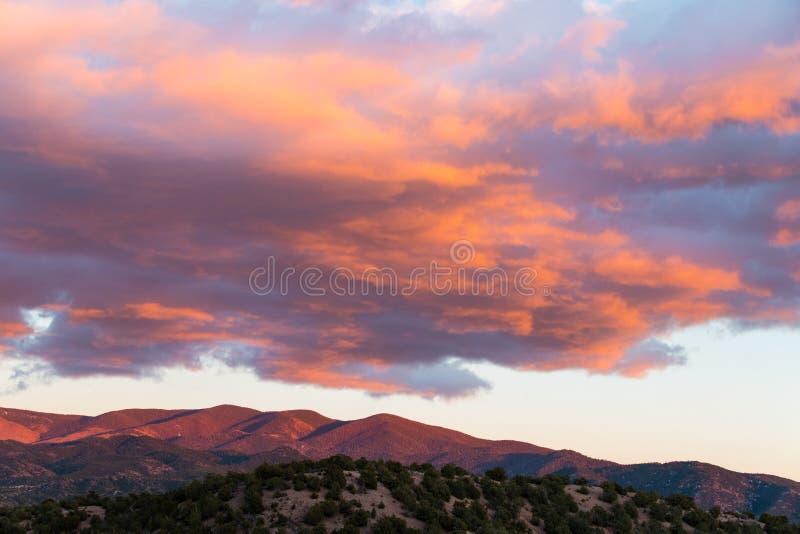 美好的日落在圣塔菲,新墨西哥附近熔铸紫色和橘黄色在云彩和山 免版税库存照片