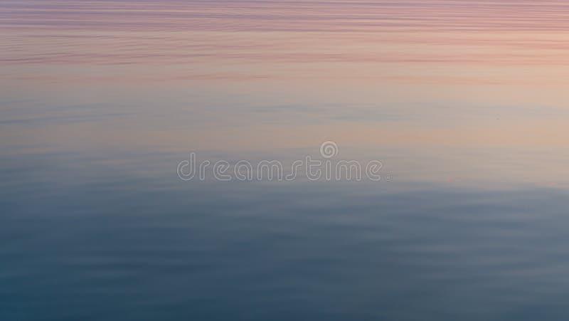 美好的日落在安静被反映的水表面反射了 免版税图库摄影