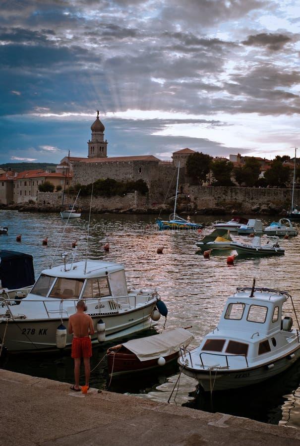 美好的日落有在岸的小镇视图,当帆船和游艇停住在海湾时 图库摄影