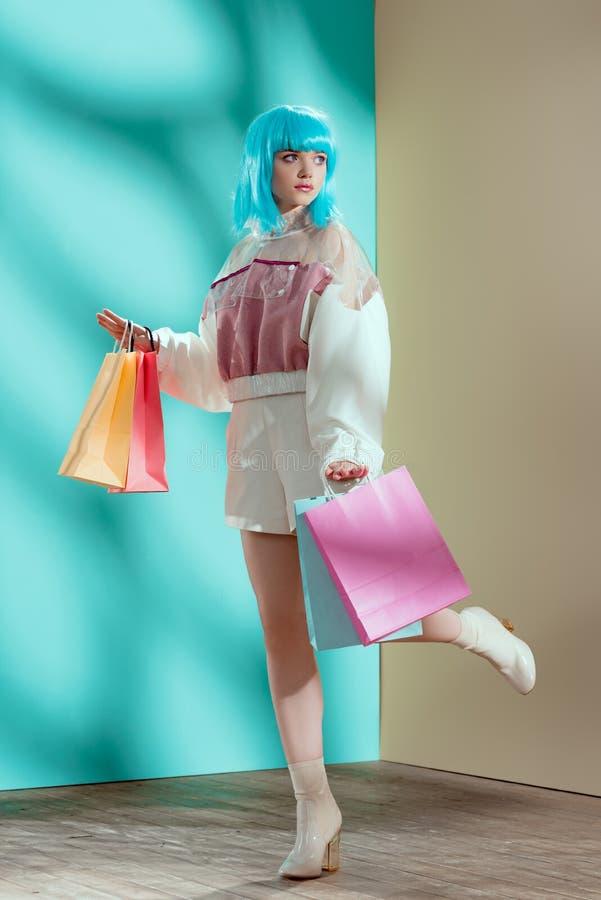 美好的时髦的年轻女性模型全长看法在拿着购物带来的蓝色假发的 免版税库存图片