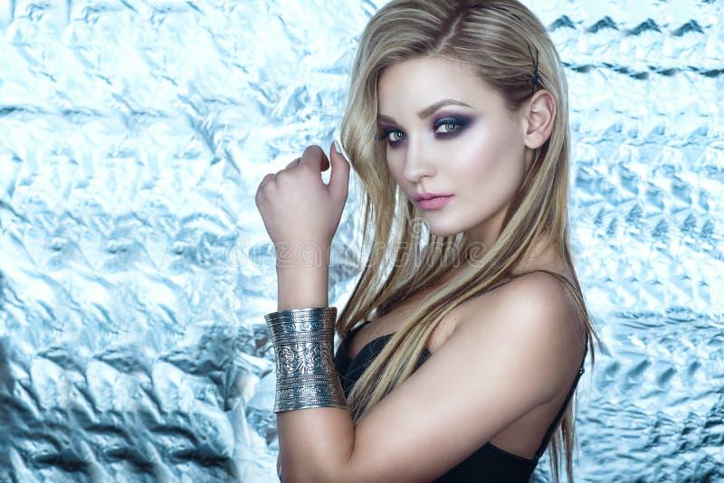 美好的时髦的白肤金发的模型与诱惑晚上做佩带的不锈钢葡萄酒袖口手镯在她的腕子 免版税库存照片