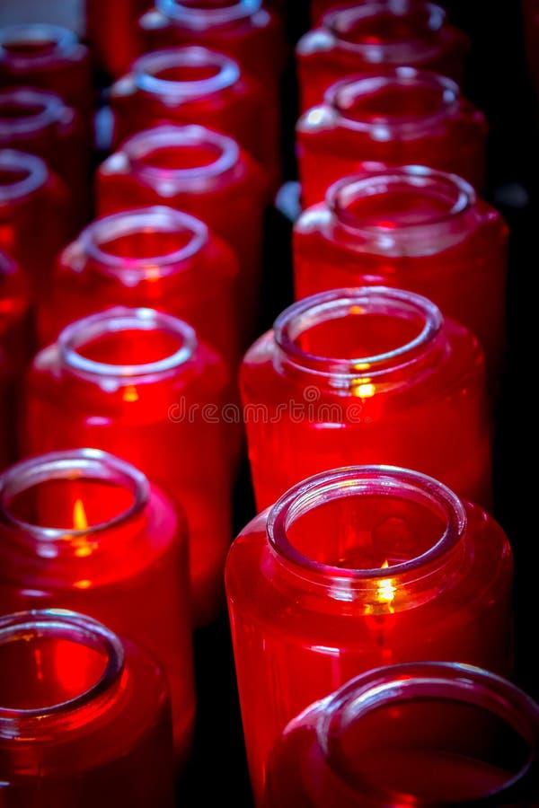 美好的明亮的红色玻璃祷告蜡烛在行排队了 库存图片