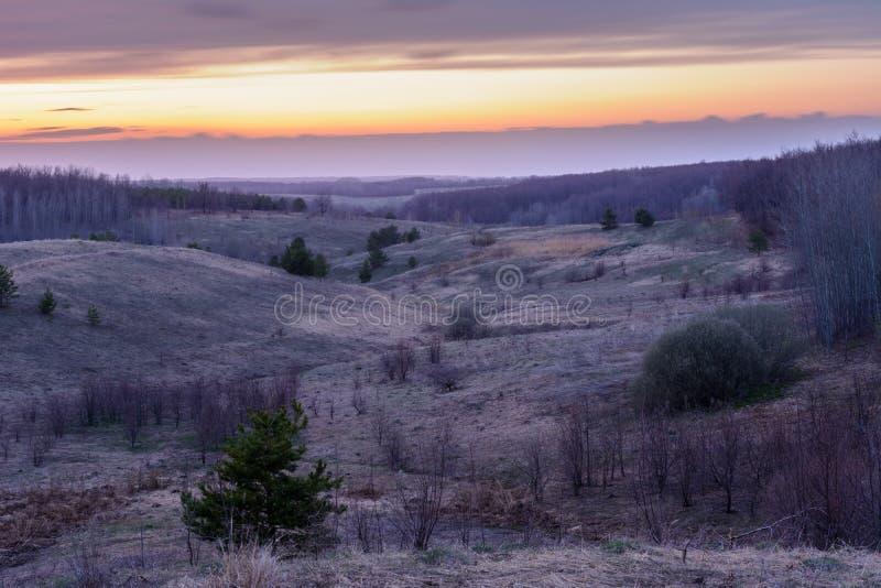 美好的春天风景:日落、树、森林、山、小山、领域、草甸和天空 与重的云彩的华美,红色天空 库存图片