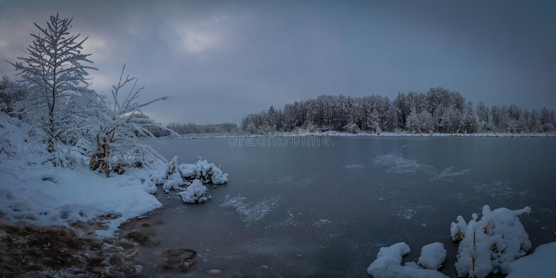 美好的晚上冬天风景 从一条冻河的多雪的海岸的看法多云天气的 库存照片