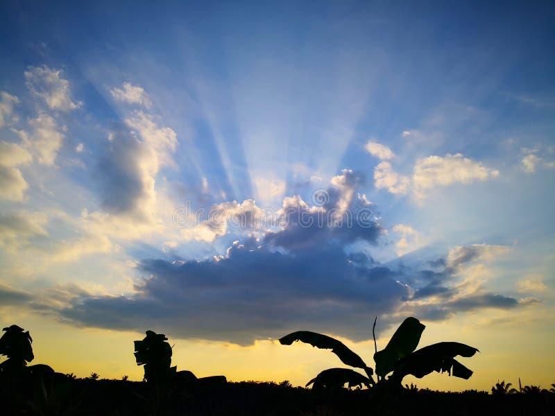 美好的晚上skyscape 太阳` s光芒亮光通过黑暗的克洛 免版税库存照片