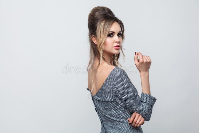 美好的有吸引力的时装模特儿旁边外形视图画象在灰色礼服的有站立的构成和的发型的,摆在和 免版税库存照片