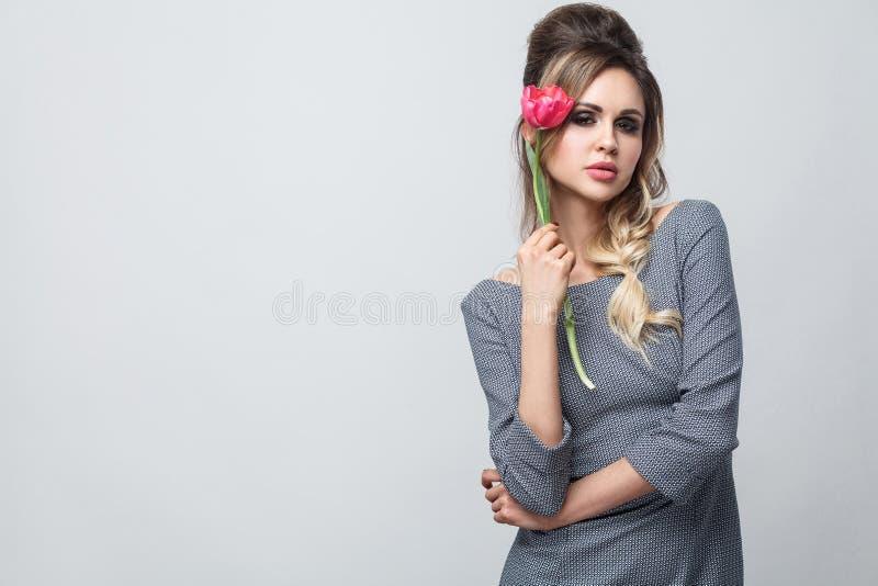 美好的有吸引力的时装模特儿画象在灰色礼服的有构成和发型的,站立,拿着红色郁金香和看 免版税库存照片