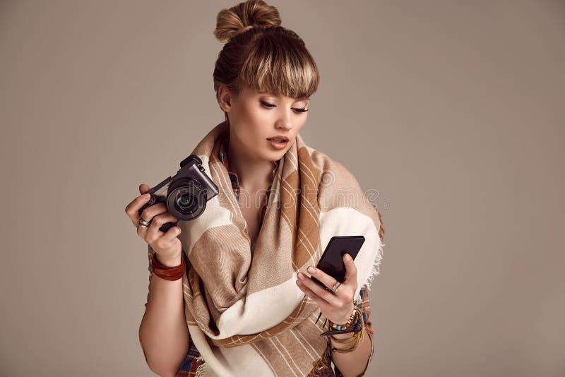 美好的有照相机和电话的魅力白肤金发的嬉皮妇女 免版税图库摄影