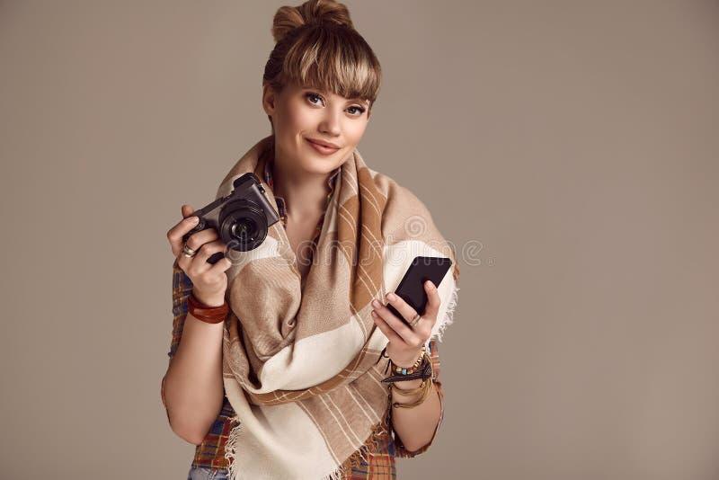 美好的有照相机和电话的魅力白肤金发的嬉皮妇女 图库摄影