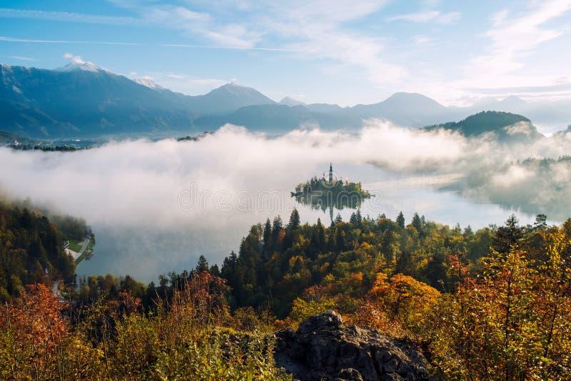 美好的有雾的日出秋天的流血的湖 免版税库存图片