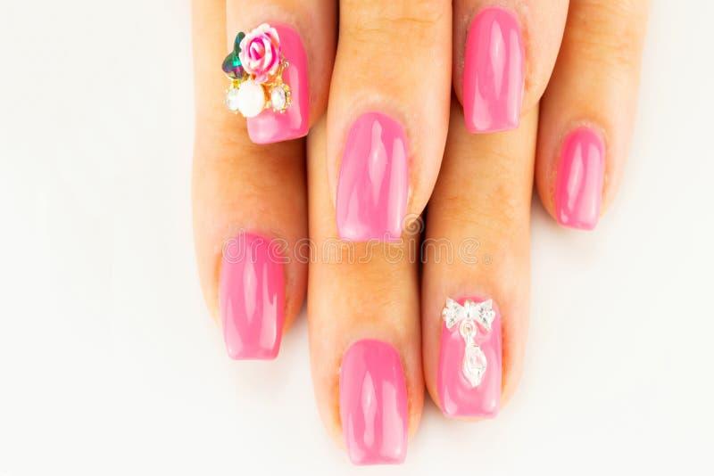 美好的桃红色钉子设计特写镜头在女性手指的在白色 库存图片