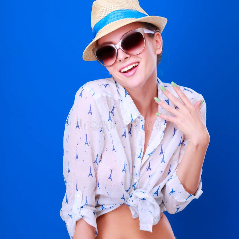 美好的模型画象在帽子的有玻璃的,隔绝在蓝色背景 免版税库存照片