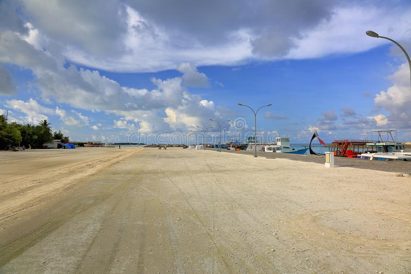 美好的横向视图 海岸线,马尔代夫, Dhangethi 黄沙路和蓝色狡猾与白色云彩 库存照片