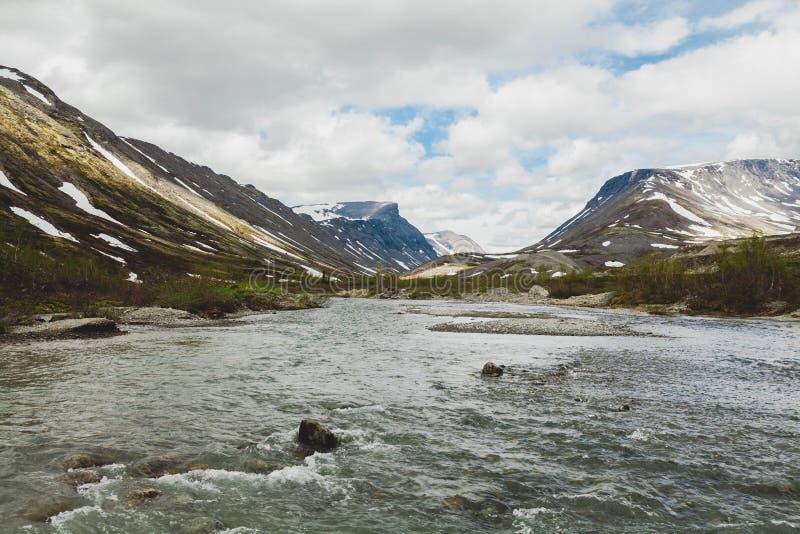 美好的横向 反对山的背景的一条风雨如磐的河 库存照片