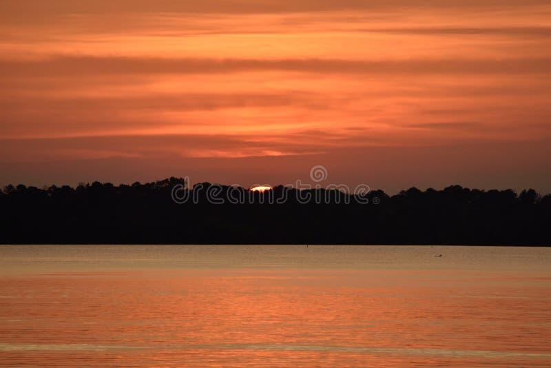 美好的橙色日落在湖的镇静水反射了 免版税库存图片