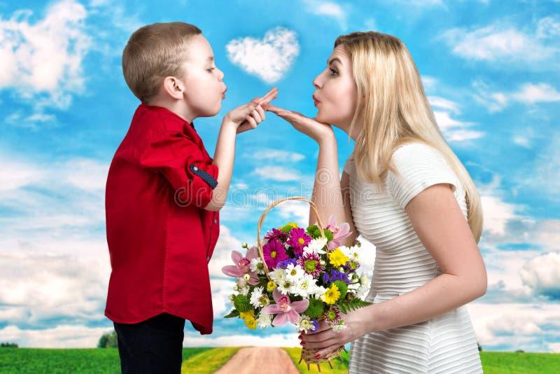 年轻美好的母亲和儿子打击亲吻 一名妇女和一个男孩有花束的,花篮子  家庭vacati的春天概念 免版税库存照片