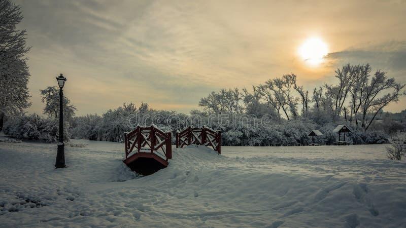美好的浪漫冬天风景 晚上城市公园由微弱的阳光点燃了 在雪下的木步行桥 小径 图库摄影