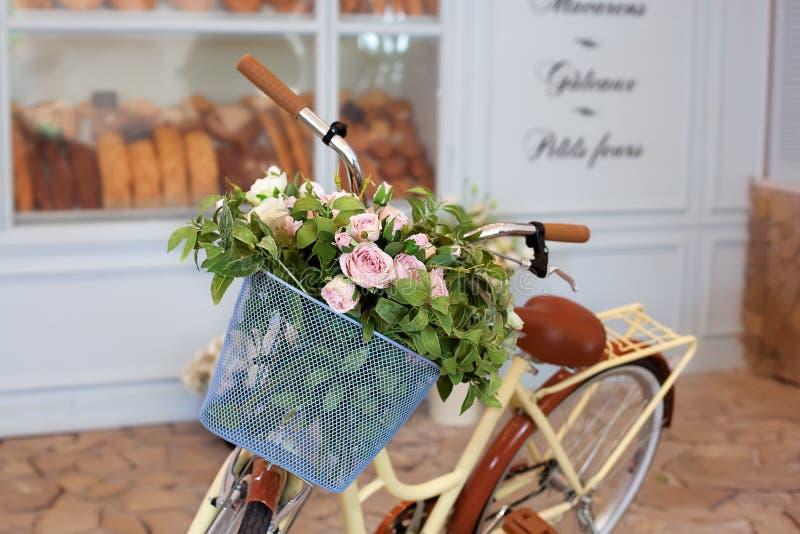 美好的浪漫风景:与花的葡萄酒柳条筐在咖啡馆附近 有花的老自行车在的一个金属篮子 免版税图库摄影