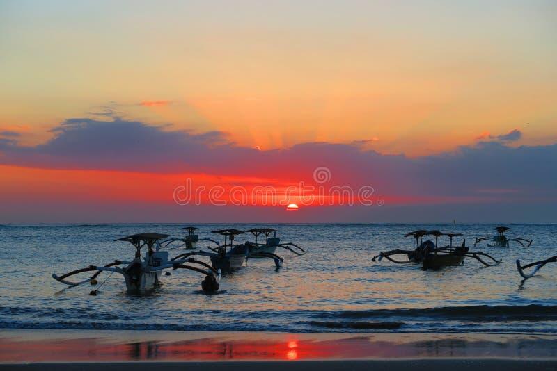 美好的海日落或日出桃红色和橙色与传统小船在巴厘岛 免版税库存照片