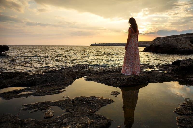 美好的海景和日落,一个女孩的剪影的背景的女孩峭壁的,在峭壁, 免版税库存照片