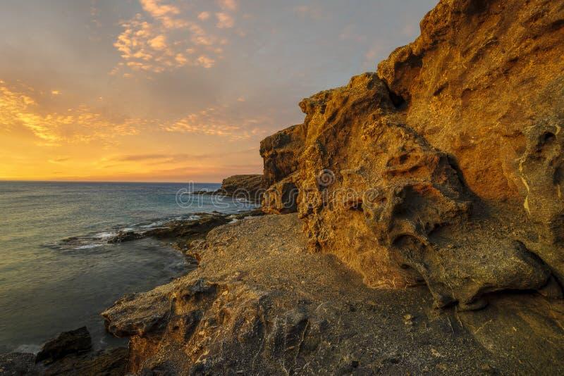 美好的海风景-在岩石海洋峭壁的日落 蓬塔帕帕加约湾 免版税库存图片
