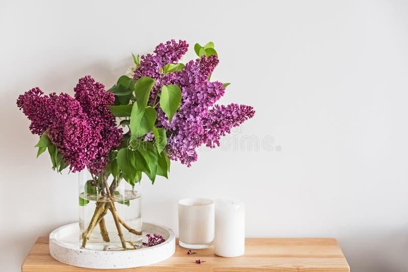 美好的淡紫色花架花束在一个玻璃花瓶的在小木立场 免版税库存图片