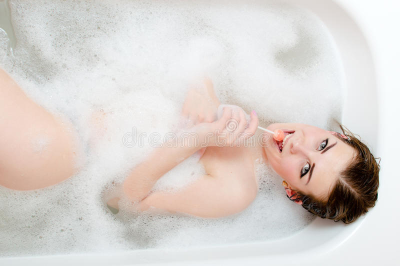 美好的温泉时间:舔糖果美丽的年轻肉欲的妇女的图片有乐趣愉快微笑的放松的&享用的说谎在温泉b 免版税库存照片
