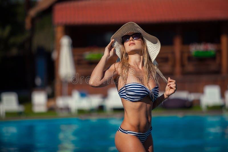 美好的游泳衣的妇女游泳池暑假summertiA美丽的少妇在游泳池边站立 免版税库存图片