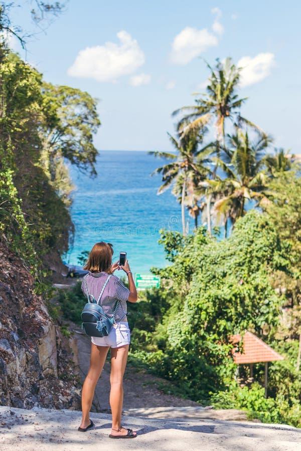 美好的热带风景年轻女人旅游照相在她的智能手机的 巴厘岛 免版税库存照片