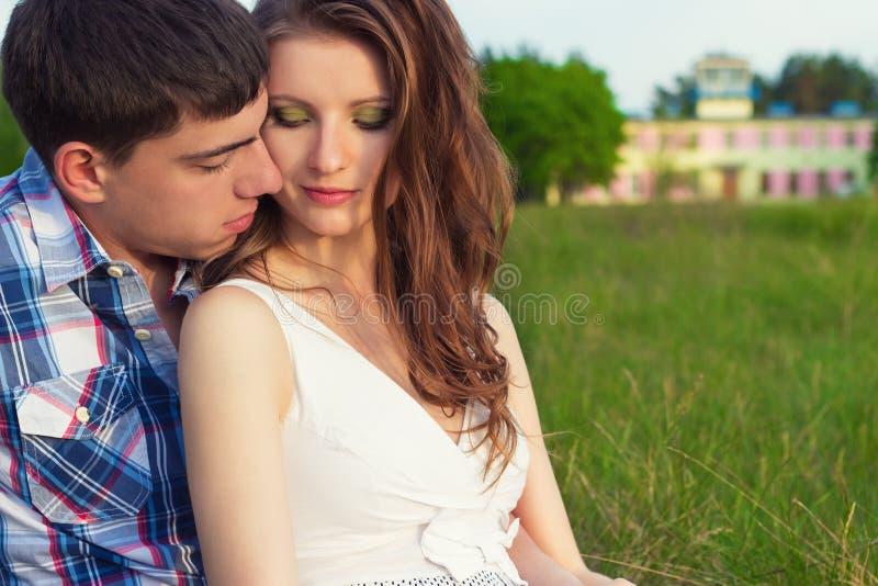 年轻美好的爱恋的愉快的夫妇在箱子坐草在温暖的晚上夏日 库存照片