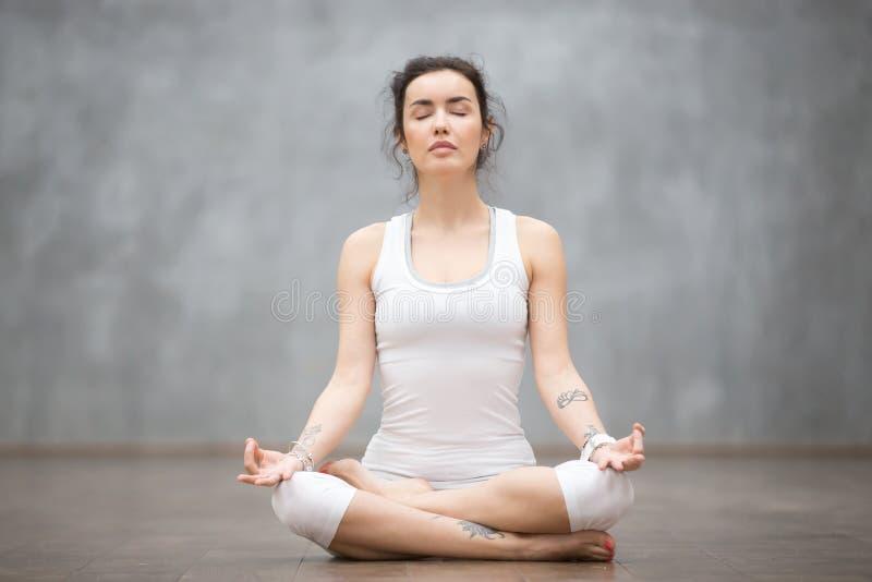 纹身花刺的解决对灰色墙壁的美丽的少妇正面图画象,休息在做瑜伽以后