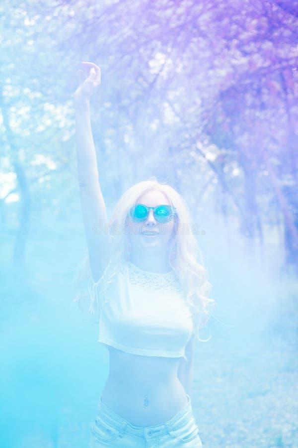 美好的白肤金发的女孩跳舞在森林蓝色紫色烟的多彩多姿的烟户外 ?? 休闲的概念 库存图片