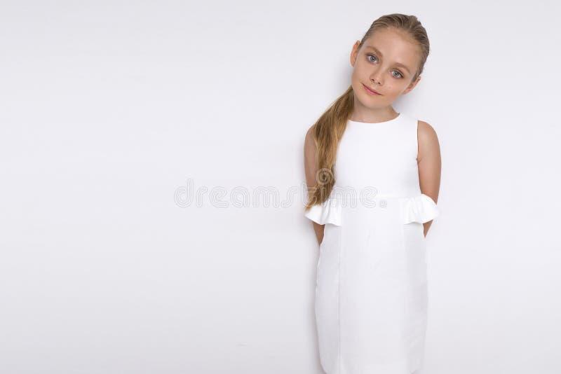 美好的白肤金发的年轻模型,逗人喜爱的女孩,在白色背景的白色礼服的 库存图片