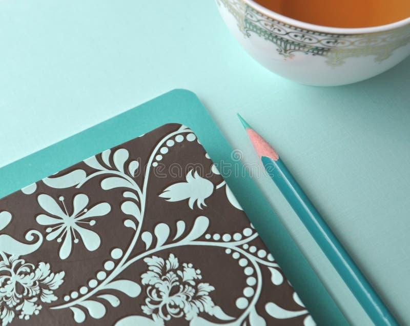 美好的白色瓷瓷杯子用茶、小野鸭铅笔、白色短信卡和水色薄荷的蓝色背景 免版税库存图片