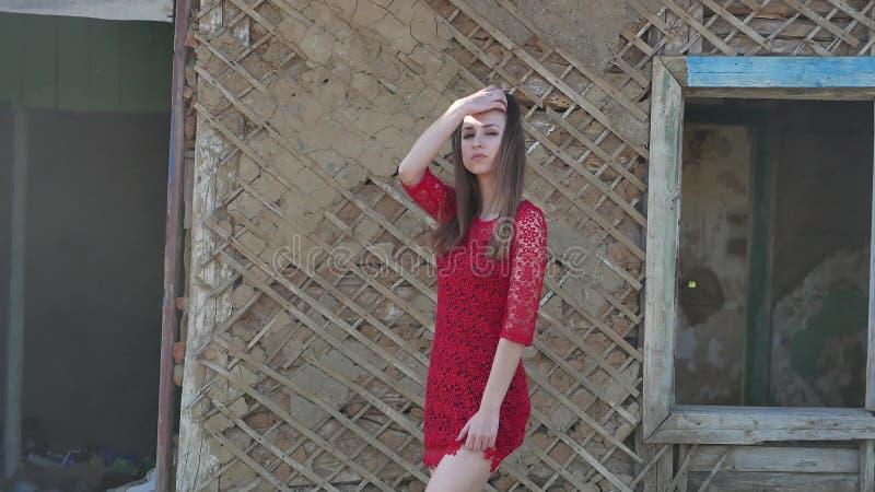 美好的礼服女孩红色 礼服的性感的女孩在废墟生活方式的老房子旁边站立 免版税库存照片