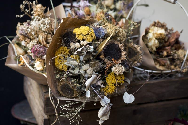 美好的秋天花束结构的干玫瑰和草甸开花与叶子,花卉背景 植物的艺术装饰 库存图片