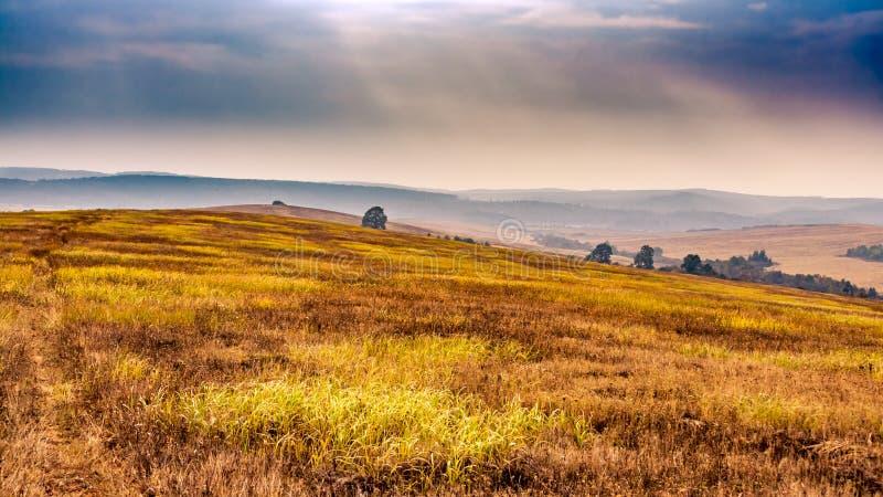 美好的秋天风景全景 软的阳光和多云天空和有雾的山在背景中 免版税库存图片
