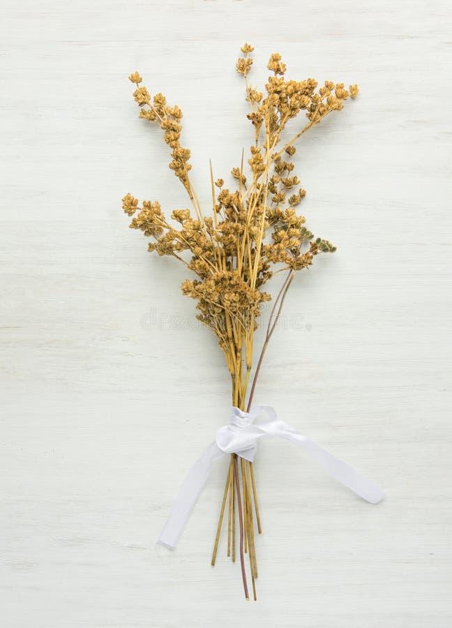 美好的秋季复活节婚礼背景 干燥野花栓与在白色木头的丝绸丝带 最低纲领派日本式 免版税库存图片