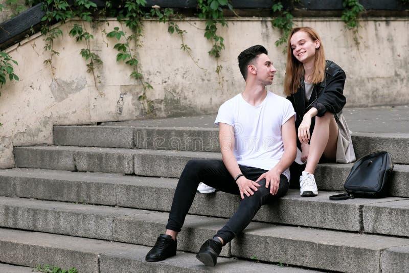 美好的红发女孩和人深色的逗人喜爱的闲谈坐台阶 免版税库存照片