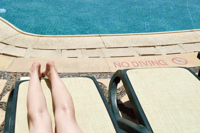美好的腿、女孩脚、妇女deckchair的背景的和水池在一个热带温暖的异乎寻常的海滨胜地,夏天 免版税库存图片